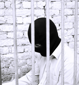 A man behind bars in a balaclava