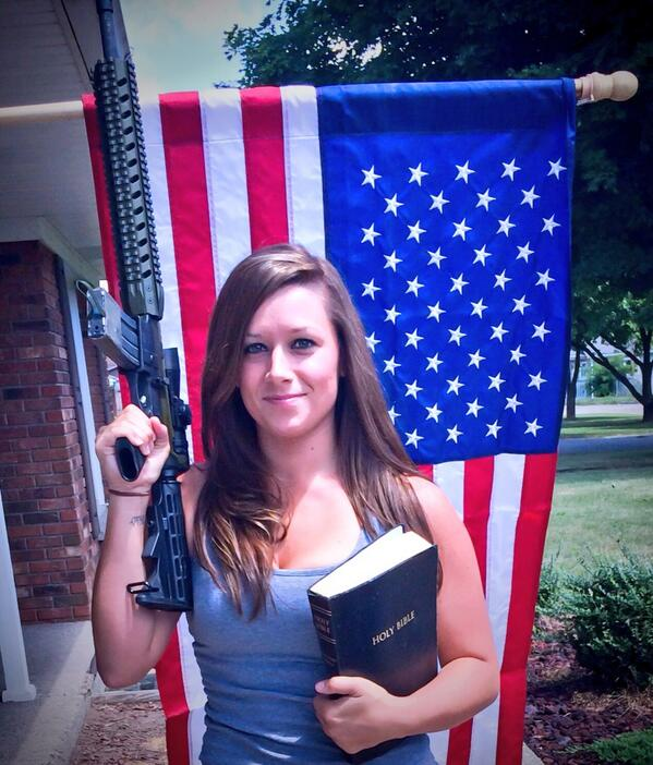 Selfie of Holly R Fisher holding a gun and bible standing in front of an American flag.